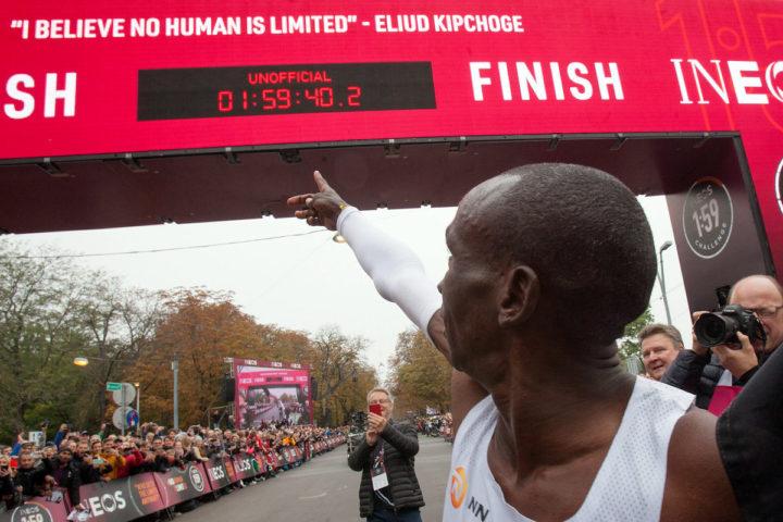 Eliud Kipchohe pointing to finish line clock